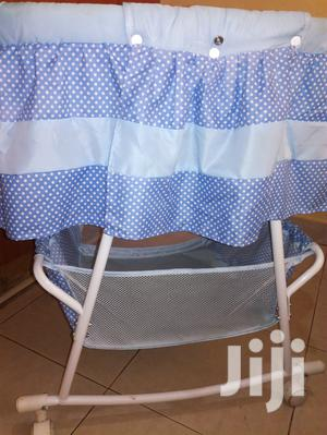 Blue Polka Dotted Baby Cot With Wheels And A Net